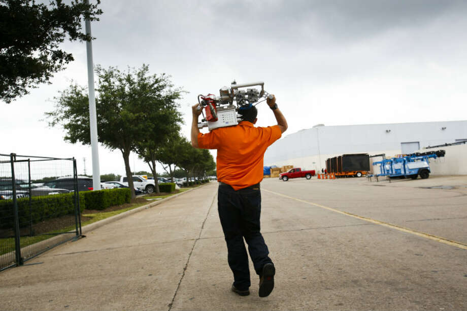 Jeff Vinyard of Applus RTD helps pack away their exhibit on the last day at the Offshore Technology Conference May 9, 2013 in Houston. (Eric Kayne/For the Chronicle)