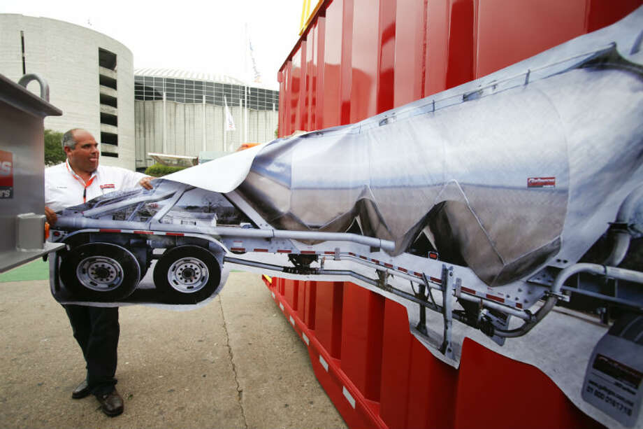 Carlos Raynal of Gallegos Trailers tears off a large picture of a pneumatic trailer on the last day at the Offshore Technology Conference May 9, 2013 in Houston. (Eric Kayne/For the Chronicle)