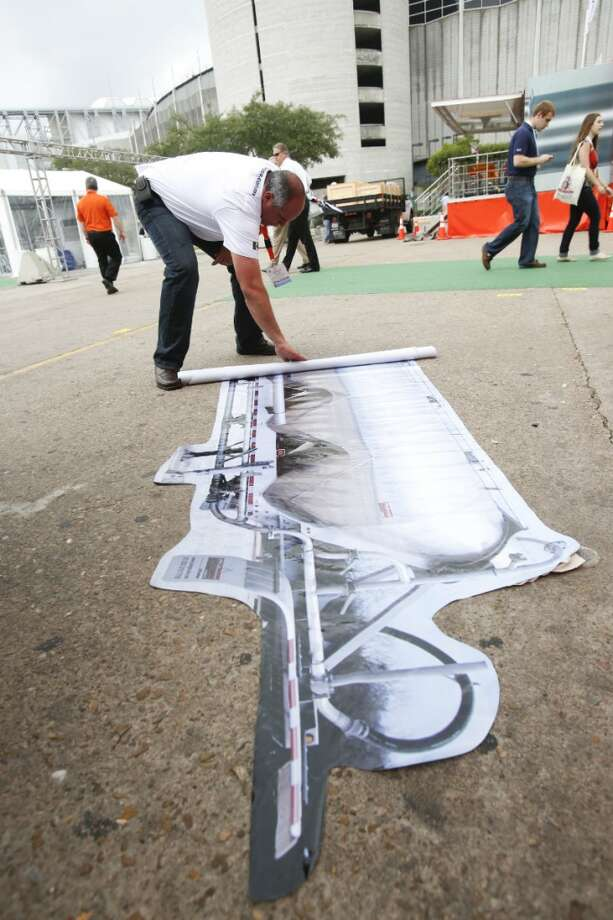 Carlos Raynal of Gallegos Trailers rolls up a large picture of a pneumatic trailer on the last day at the Offshore Technology Conference May 9, 2013 in Houston. (Eric Kayne/For the Chronicle)