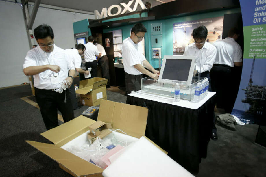 Employees of Moxa tear down their booth on the last day at the Offshore Technology Conference May 9, 2013 in Houston. (Eric Kayne/For the Chronicle)