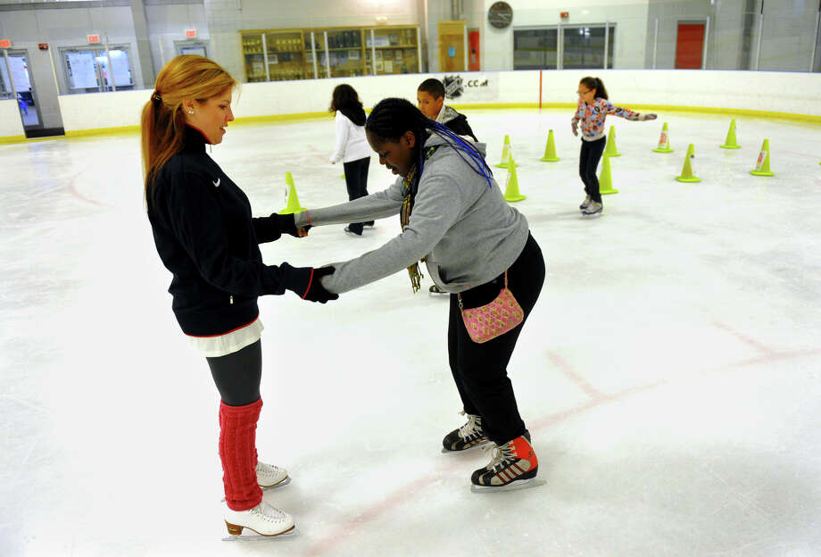 Luis Marin School student Jakari Ludd, 12, gets a little help from former Olympic skater Melissa Gregory in the last session of the eight week EduSkating program held at the Wonderland of Ice in Bridgeport, Conn. on Thursday May 8, 2013. Photo: Christian Abraham / Connecticut Post