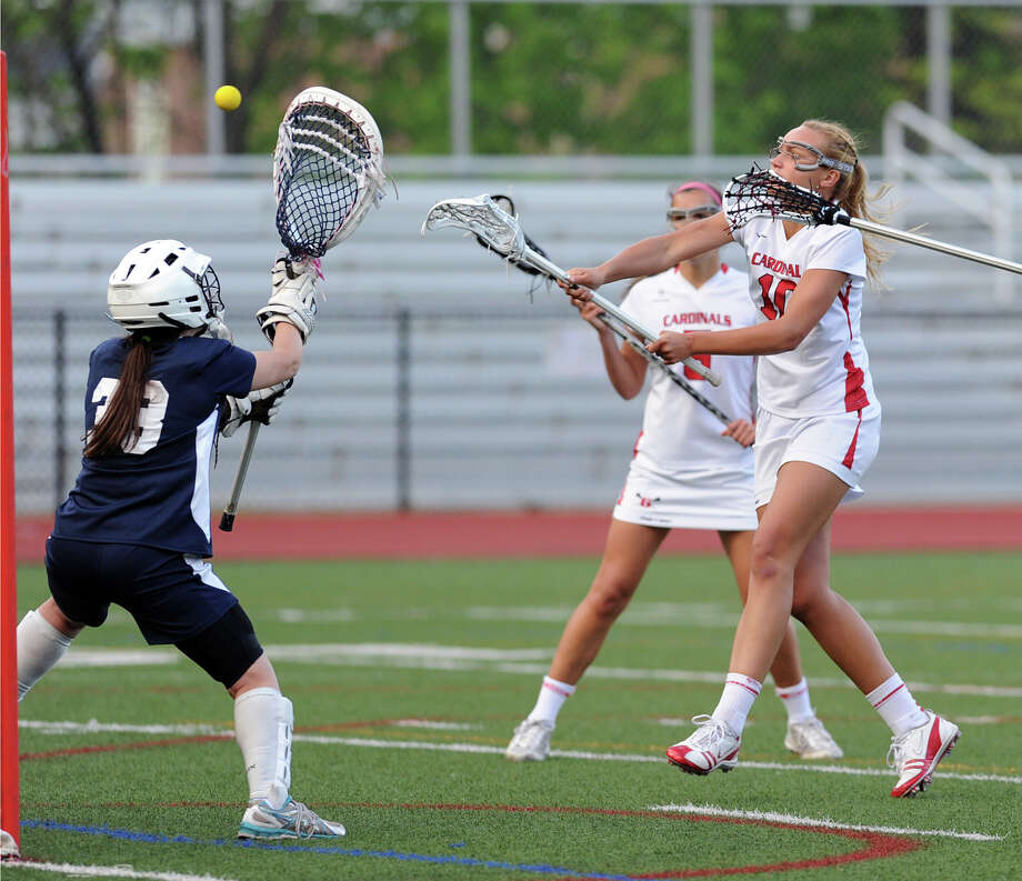 At right, Emily Johnson of Greenwich shoots and scores the first goal of the game for Greenwich past Staples goalie Emma Boland during the girls high school lacrosse match between Greenwich High School and Staples High School at Greenwich, Thursday, May 9, 2013. Photo: Bob Luckey / Greenwich Time