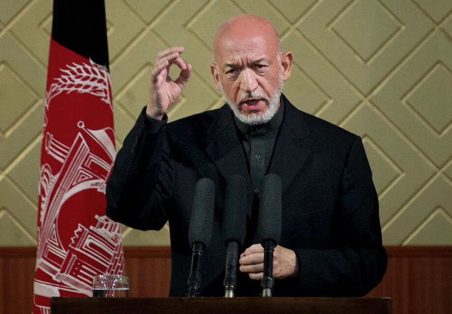 "Afghan President Hamid Karzai gestures during a ceremony at Kabul University in Kabul, Afghanistan, Thursday, May 9, 2013. Karzai said he is ready to let the U.S. have nine bases in the country after the 2014 combat troop pullout, but wants Washington's ""security and economic guarantees"" first.  (AP Photo/Anja Niedringhaus) Photo: Anja Niedringhaus"