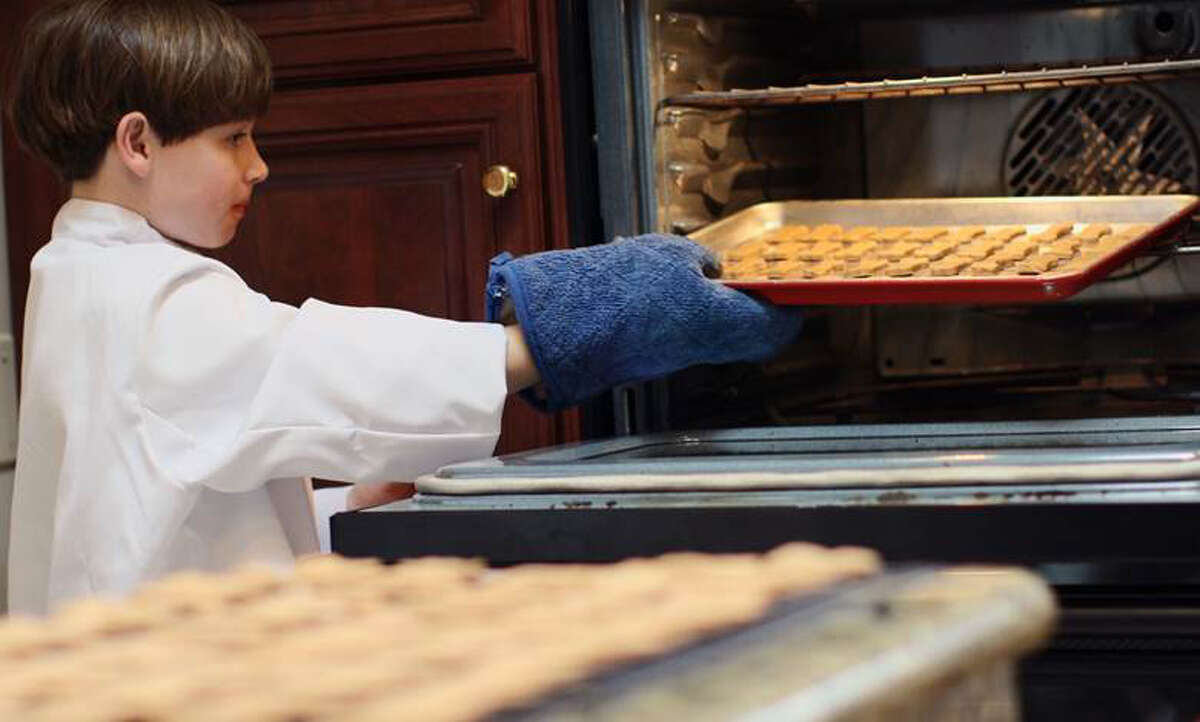 Stamford resident Ryan Kelley, 11, owner of Ryan's Barkery, bakes the company's best-selling peanut butter treats. His 18-month-old beagle, Barkley, often fills in as a taste tester.