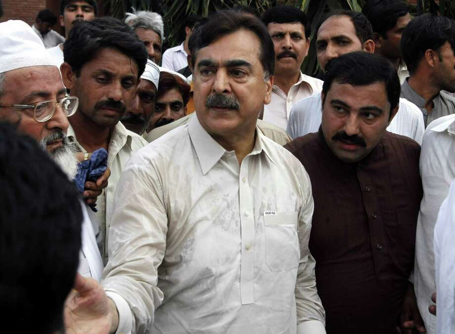 People visit Pakistan's former Prime Minister Yousuf Raza Gilani, center, at his residence in Multan, Pakistan, Thursday, May 9, 2013. Gunmen attacked an election rally in Pakistan's southern Punjab province on Thursday and abducted Ali Haider Gilani,  son of a former prime minister, intensifying what has already been a violent run-up to Saturday's nationwide elections. (AP Photo/Zeeshan Hussain) Photo: Zeeshan Hussain