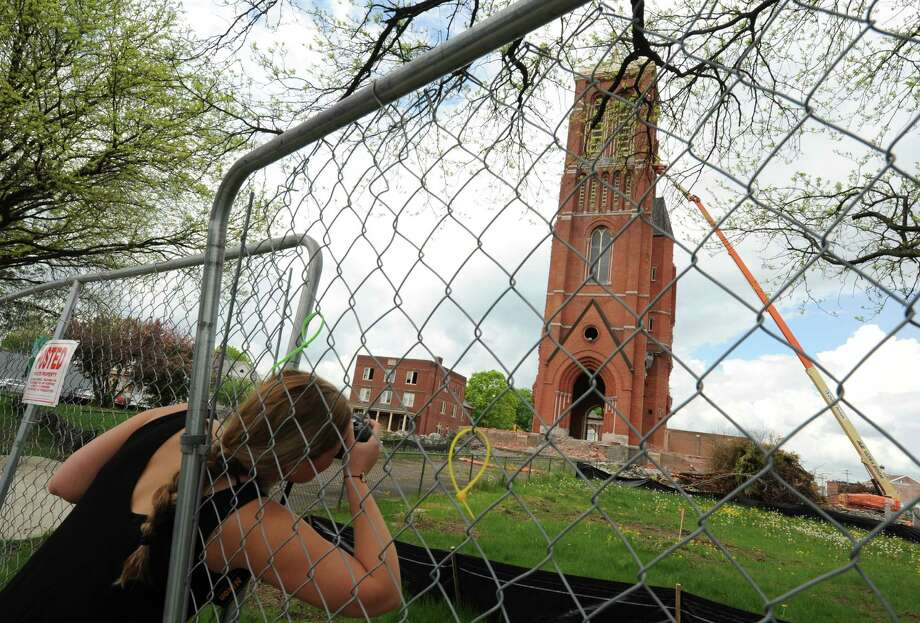 Siena student Eden Alaxanian reaches through a space in the fence to photograph the demolition of the former St. Patrick's Church on Thursday May 9, 2013 in Watervliet N.Y. (Michael P. Farrell/Times Union) Photo: Michael P. Farrell