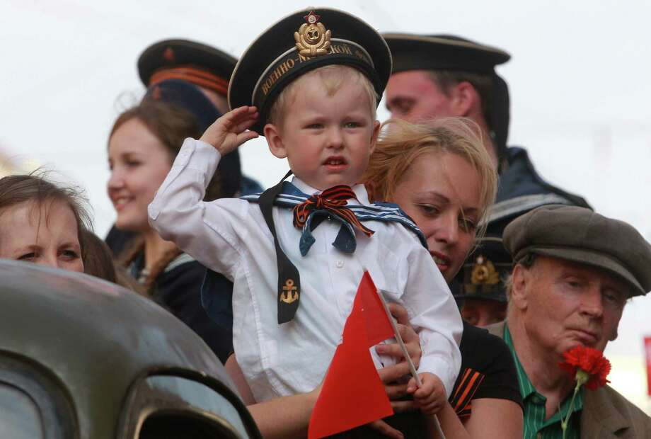 A child wearing Soviet Navy style uniform salutes during celebration of the Victory Day in St.Petersburg, Russia, Thursday, May 9, 2013. Russia is celebrating the anniversary of victory over Germany in WWII. Photo: Dmitry Lovetsky, Associated Press / AP