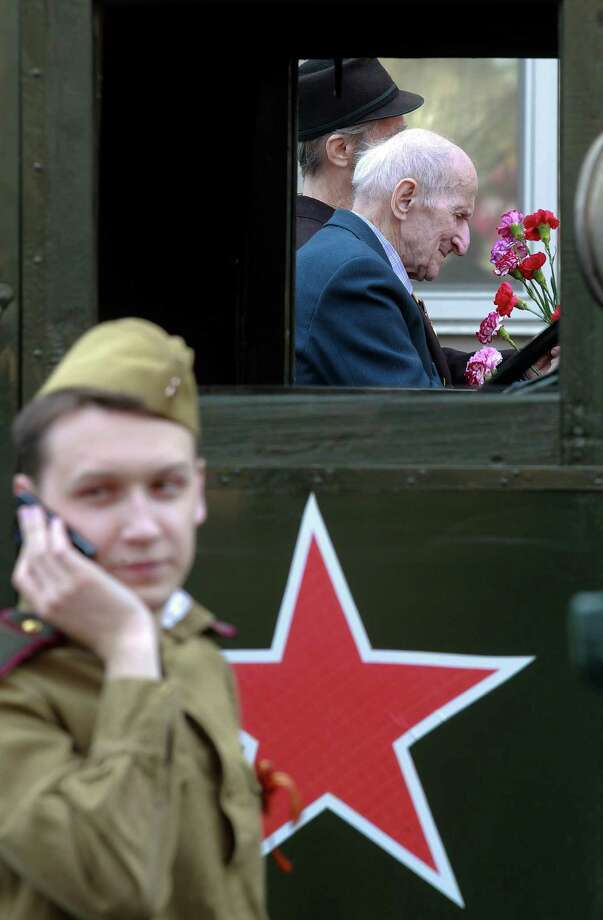 World War II veterans ride a car as a member of a historical military club wearing Soviet army uniform speaks on a phone during the celebration of Victory Day in St.Petersburg, Russia, Thursday, May 9, 2013. Russia is celebrating the anniversary of victory over Germany in WWII. Photo: Dmitry Lovetsky, Associated Press / AP