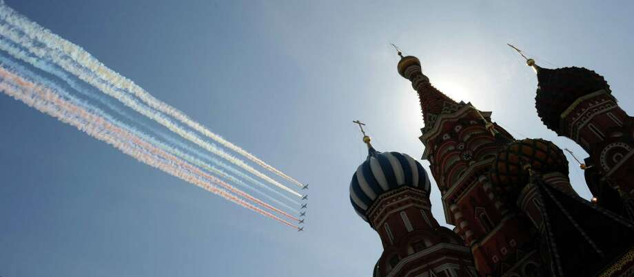 Russian military jets fly above the St.Basil's cathedral at the Red Square in Moscow, on May 9, 2013, during Victory Day parade. Fighter jets screamed over Red Square and heavy tanks rumbled over its cobblestones as Russia flexed today its military muscle on the anniversary of its costly victory over Nazi Germany in World War II. Photo: YURI KADOBNOV, AFP/Getty Images / AFP