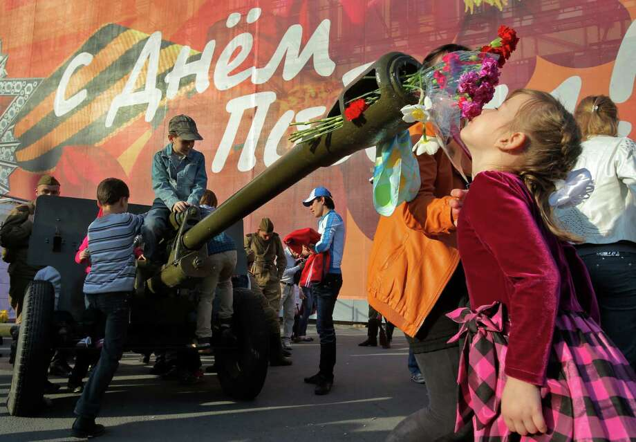 A girl smells the flowers insert?d to the barrel of an artillery canon during celebration of the Victory Day in St.Petersburg, Russia, Thursday, May 9, 2013. Russia is celebrating the anniversary of victory over Germany in WWII. The poster reads: ' Congratulation with Victory Day!'. Photo: Dmitry Lovetsky, Associated Press / AP