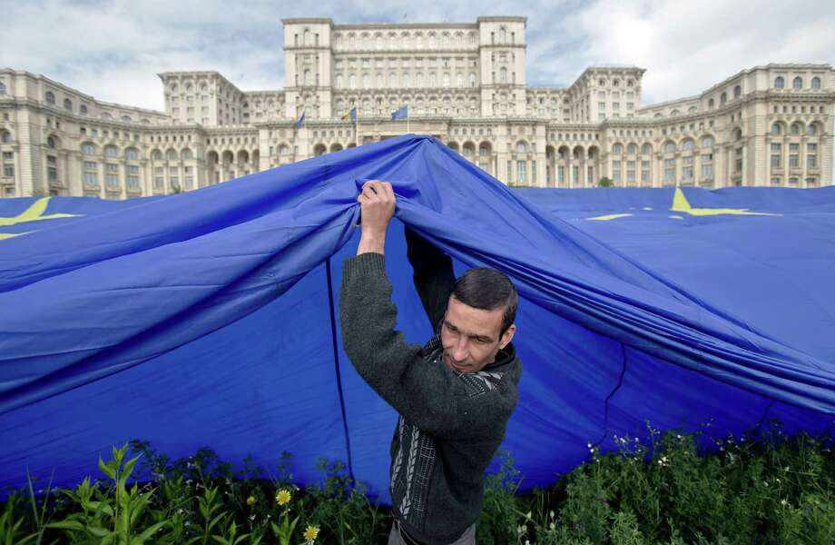 A worker pulls a huge European Union flag, in Bucharest, Romania, Thursday, May 9, 2013, while installing it in front of the Romanian parliament building, formerly the House of the People, built during the rule of communist dictator Nicolae Ceausescu. The flag, with a weight of 800 kg and measuring 100 by 140 meters, was sponsored by a private television network and was placed at the parliament to mark Europe Day. Romania joined the European Union in 2007. Photo: Vadim Ghirda, Associated Press / AP