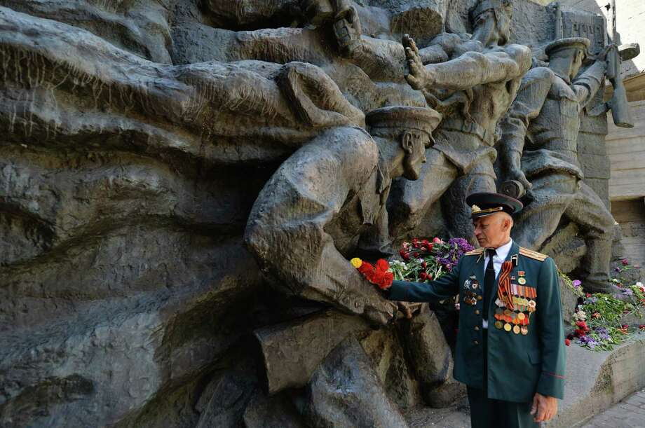 A World War II veteran lays flowers to the Victory Da monument in Kiev on May 9, 2013. Ukraine, Russia and other Soviet Union countries today celebrate the victory over Nazi Germany in World War II. Photo: SERGEI SUPINSKY, AFP/Getty Images / AFP