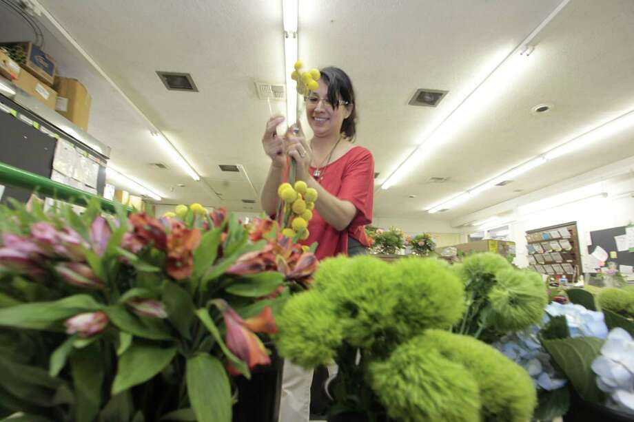 Carissa Gonzalez of Scent of a Flower creates a Mother's Day arrangement at Johnathan Andrew Sage Inc., the shop she shares with Johnathan Sage. Photo: Billy Smith II, Staff / © 2013 Houston Chronicle