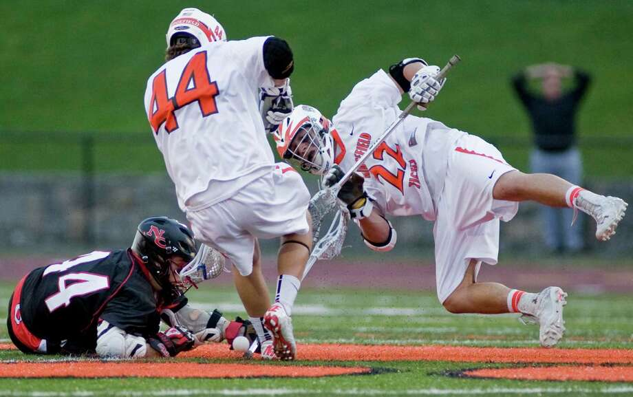 New Canaan High School's Teddy Bossidy, Ridgefield High School's Martin Carbone and Will Bonaparte all scramble for the loose ball during a game played at Ridgefield. Thursday, May 9, 2013 Photo: Scott Mullin / The News-Times Freelance