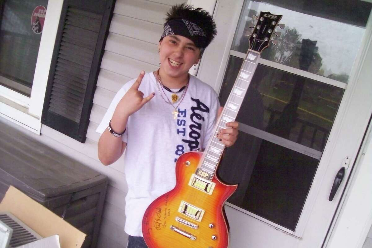 Joey Pettinato with his new guitar signed by the Trans-Siberian Orchestra. Joey has Tourette syndrome and is home-schooled because of the taunts from his classmates, but is at ease when he plays guitar. (Picture courtesty of Roger Pettinato).