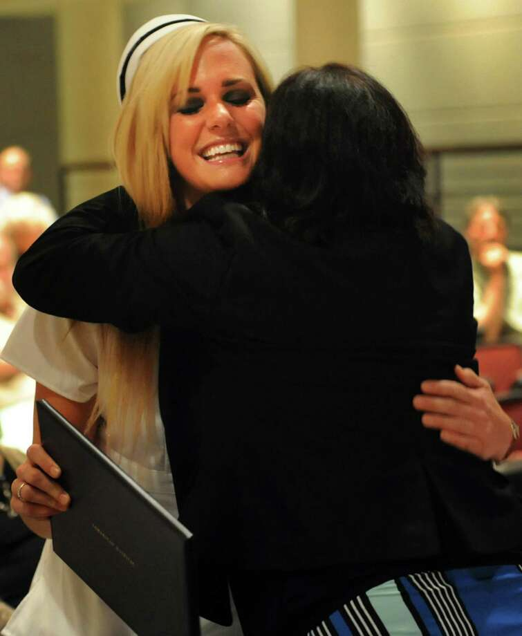 Graduate Sasha Hebert, left, receives her diploma, pin and a hug from faculty member Shanon Kress during the Samaritan Hospital School of Nursing college commencement on Thursday, May 9, 2013, at Hudson Valley Community College in Troy, N.Y. (Cindy Schultz / Times Union) Photo: Cindy Schultz / 10022131A