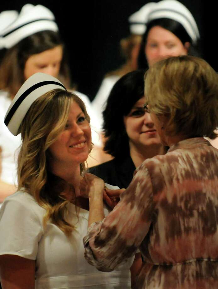 Graduate Lauren Stealey, left, receives her pin from faculty member Kathy Borge, right, during the Samaritan Hospital School of Nursing college commencement on Thursday, May 9, 2013, at Hudson Valley Community College in Troy, N.Y. (Cindy Schultz / Times Union) Photo: Cindy Schultz / 10022131A