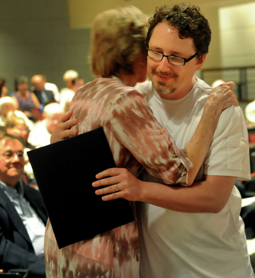 Graduate David Thurlow, right, receives his diploma, pin and a hug from faculty member Kathy Borge during the Samaritan Hospital School of Nursing college commencement on Thursday, May 9, 2013, at Hudson Valley Community College in Troy, N.Y. (Cindy Schultz / Times Union) Photo: Cindy Schultz / 10022131A
