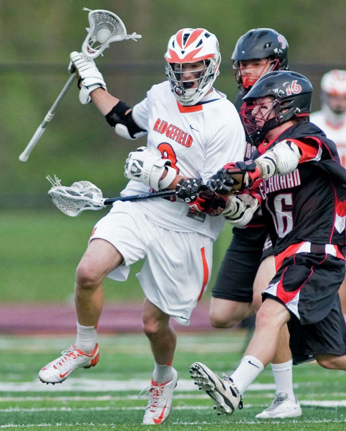 Ridgefield High School's Tim Cozens tries to get by New Canaan High School's Henry Stanton during a game against , played at Ridgefield. Thursday, May 9, 2013