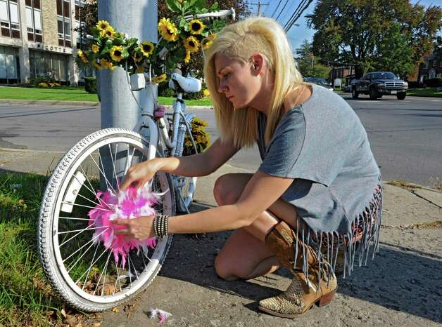 Margaret Partyka of Albany puts a new boa in the spokes of a ghost bike, Monday Oct. 10, 2011, in memory of the late Diva DeLoayza who was killed while riding a bike near the University Plaza in Albany, N.Y. Partyka owns the boutique Some Girls which was previously owned by DeLoayza. (Lori Van Buren / Times Union) Photo: Lori Van Buren / 00014900A