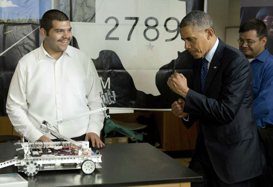 President Barack Obama pretends to spar with a robot while viewing student projects at Manor New Tech High outside Austin. Photo: SAUL LOEB, Staff / AFP