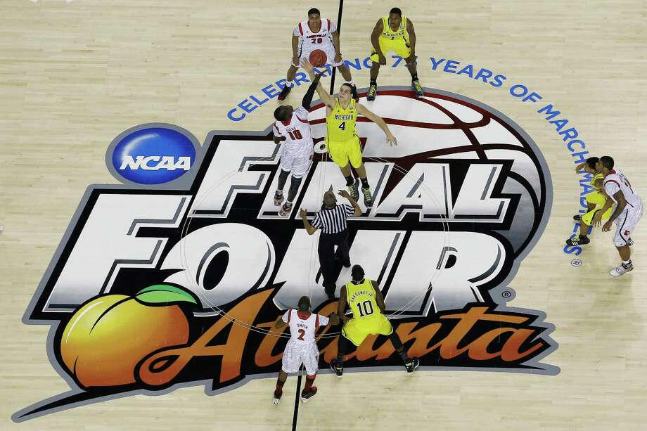 FILE - In this April 8, 2013, file photo, Louisville's Gorgui Dieng, center left, and Michigan's Mitch McGary (4), leap for the opening tip-off in the first half of the national championship game of the NCAA college basketball tournament at the Final Four in Atlanta. The Final Four's first two games are moving to cable next year. CBS and Turner Sports say the national semifinals will air on TBS in 2014 and 2015, with the title game remaining on CBS.  (AP Photo/David J. Phillip, File) Photo: David J. Phillip / AP