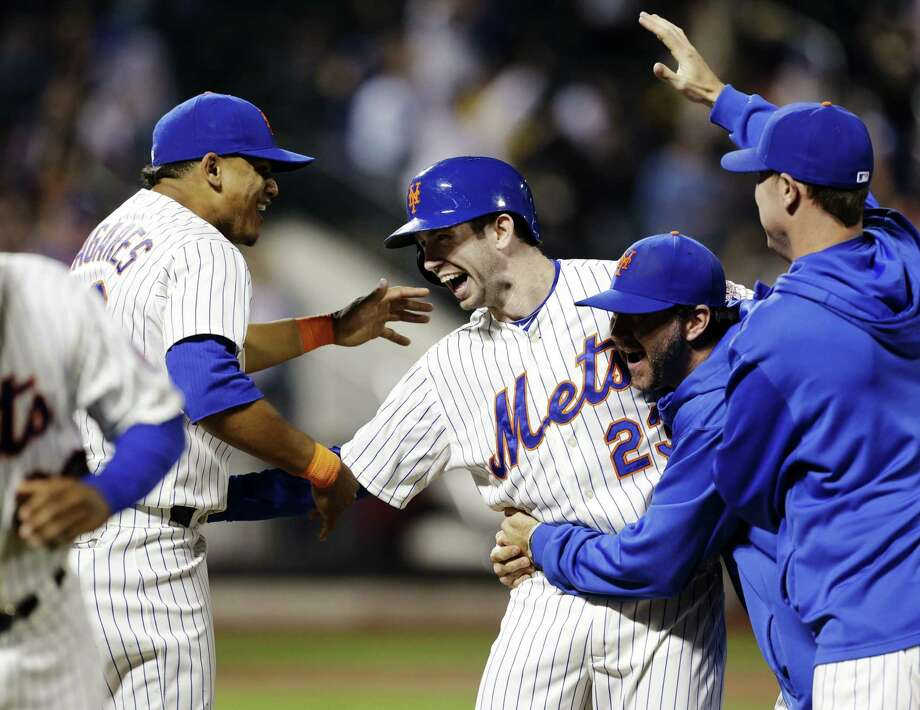 New York Mets' Mike Baxter, center, celebrates with teammates after hitting a walk-off single during the ninth inning of a baseball game against the Pittsburgh Pirates at Citi Field, Thursday, May 9, 2013, in New York. The Mets won 3-2. (AP Photo/Seth Wenig) Photo: Seth Wenig