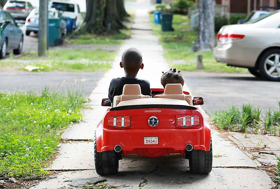 "The babe magnet: Five-year-old Antonio Garner Jr. takes Azariyah King, 1, for a spin in his Power Wheels Ford Mustang in Durham, N.C. ""When he drives it, every one honks and waves, and girls ask him for a ride,"" says his mother, Shamika Lyons. Photo: Christine T. Nguyen, Associated Press"