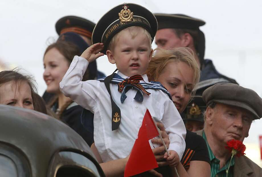 A child wearing Soviet Navy style uniform salutes during celebration of the Victory Day in St.Petersburg, Russia, Thursday, May 9, 2013. Russia is celebrating the anniversary of victory over Germany in WWII. Photo: Dmitry Lovetsky, Associated Press