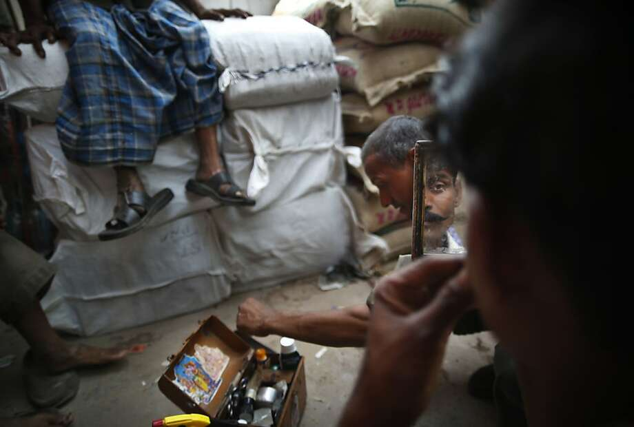 A daily wage worker looks at his reflection in a mirror after a shave from a roadside barber at a wholesale market in New Delhi, India, Thursday, May 9, 2013. Photo: Saurabh Das, Associated Press