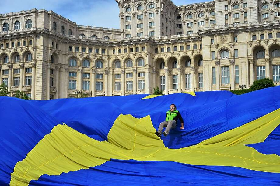 A man jumps over a star on a giant flag of the European Union (EU) in front of the Parliament building in Bucharest May 9, 2013. A private TV station installed a EU flag weighing 800 kilograms and measuring 100 meters wide and 140 meters long to mark The Europe Day. Huge pieces of cloth were put together by a few seamstresses from a flags factory. The stars, symbol of the European Union, were sewn by hand after the flag was dropped on Aerodrome Clinceni near Bucharest.  Photo: Daniel Mihailescu, AFP/Getty Images