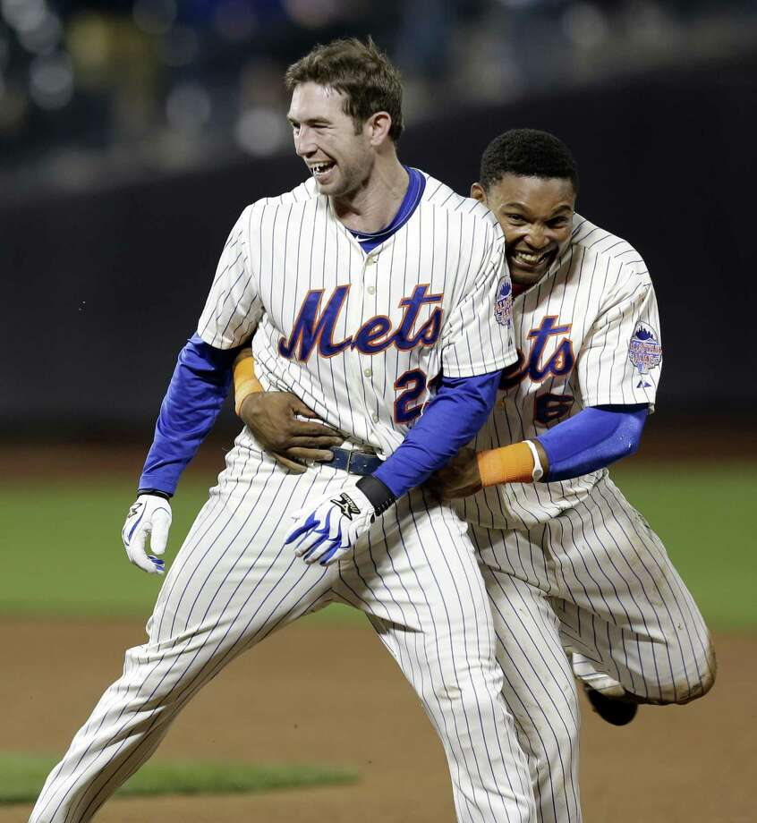 The Mets' Marlon Byrd, right, embraces Mike Baxter's second winning pinch hit in three days. Baxter's ninth-inning single toppled the Pirates 3-2 on Thursday. Photo: Seth Wenig, STF / AP
