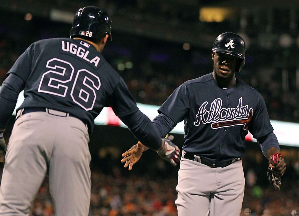 Atlanta Braves Dan Uggla (26) greets Juntin Upton (8) at home plate after he scored off a RBI single by Freddie Freeman in the 5th inning of their MLB baseball game with the San Francisco Giants Thursday, May 9, 2013 in San Francisco, Calif.