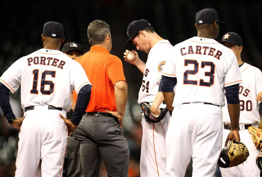 Astros starting pitcher Lucas Harrell (64) is checked out by Nate Lucero after getting hit by a come backer. Photo: Karen Warren, Houston Chronicle