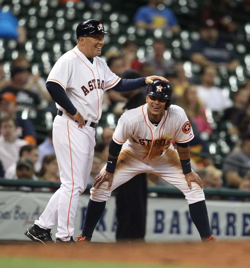 Astros third base coach Dave Trembley (47) pats  shortstop Ronny Cedeno (13) on the head at third base.