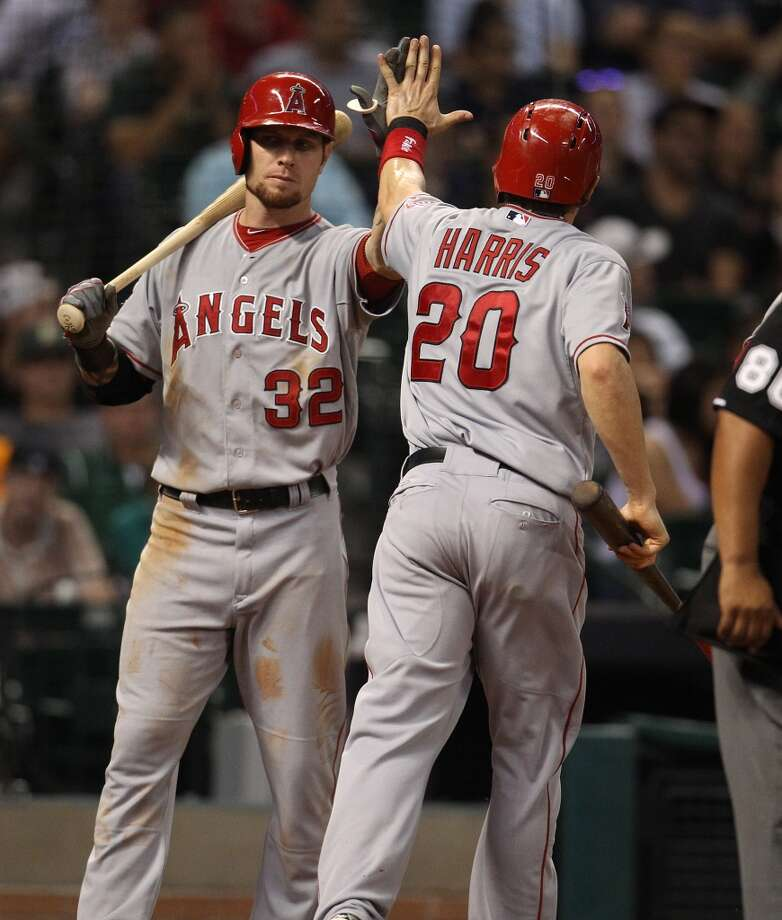 Angels shortstop Brendan Harris (20) celebrates his run scored with right fielder Josh Hamilton after an RBI double by Mark Trumbo. Photo: Karen Warren, Houston Chronicle