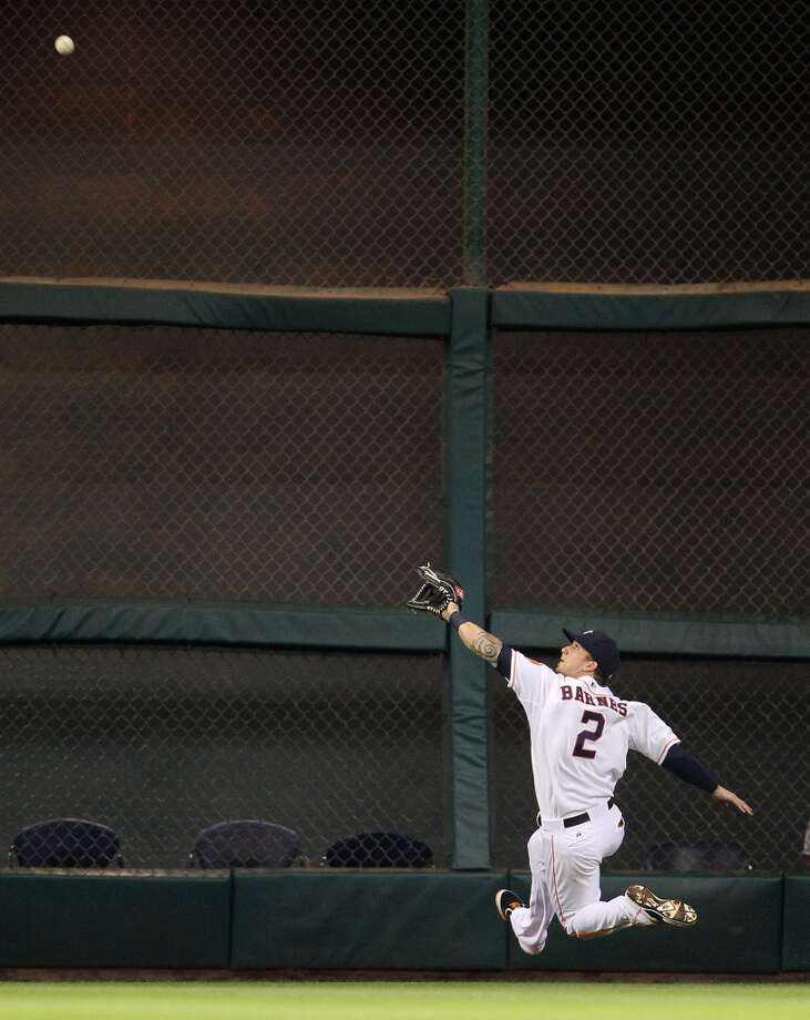Astros right fielder Brandon Barnes (2) leaps to make a catch on a sac fly by Angels third baseman Alberto Callaspo.