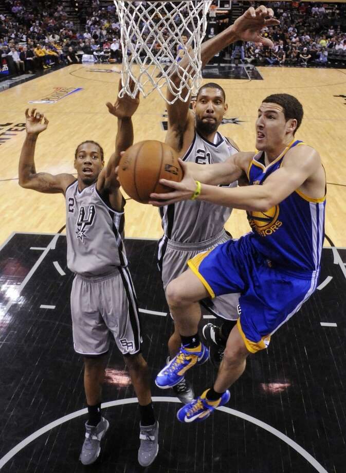 The Warriors' Klay Thompson shoots around the Spurs' Kawhi Leonard and Tim Duncan during second half action of Game 2 in the NBA Western Conference semifinals Wednesday May 8, 2013 at the AT&T Center. The Warriors won 100-91.