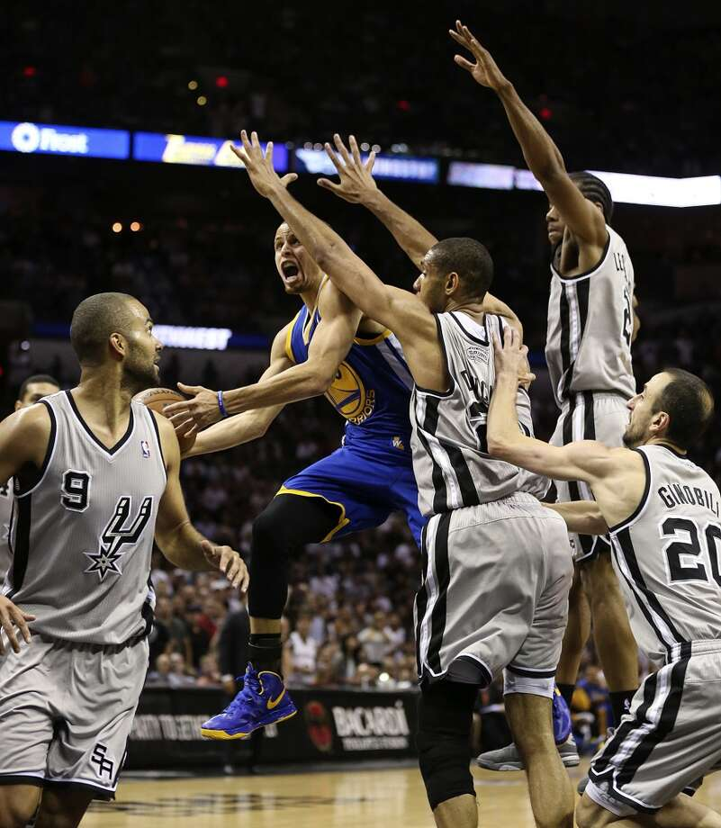 Surrounded by Spurs defenders, the Warriors' Stephen Curry scores during the second half of Game 2 in the NBA Western Conference semifinals at the AT&T Center, Wednesday, May 8, 2013. The Warriors won, 100-91 to even the series at 1-1.