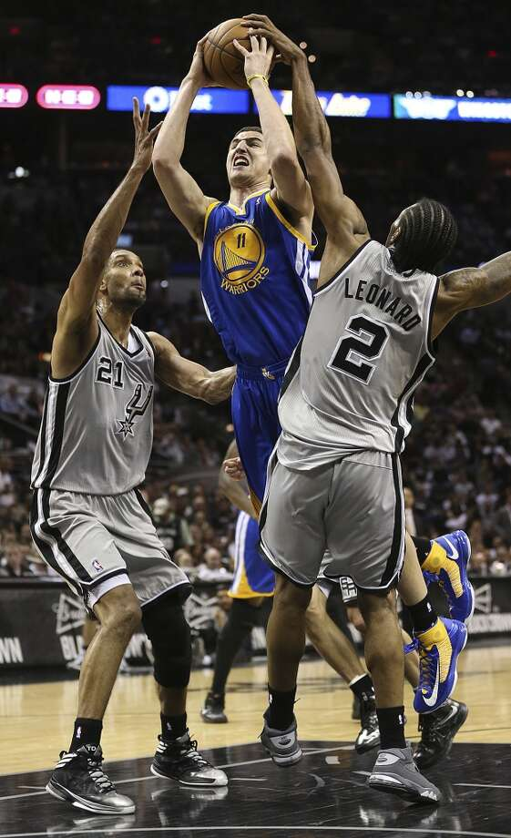 The Warriors' Klay Thompson drives between the Spurs' Tim Duncan and Kawhi Leonard during the second half of Game 2 in the NBA Western Conference semifinals at the AT&T Center, Wednesday, May 8, 2013. The Warriors won, 100-91 to even the series at 1-1.