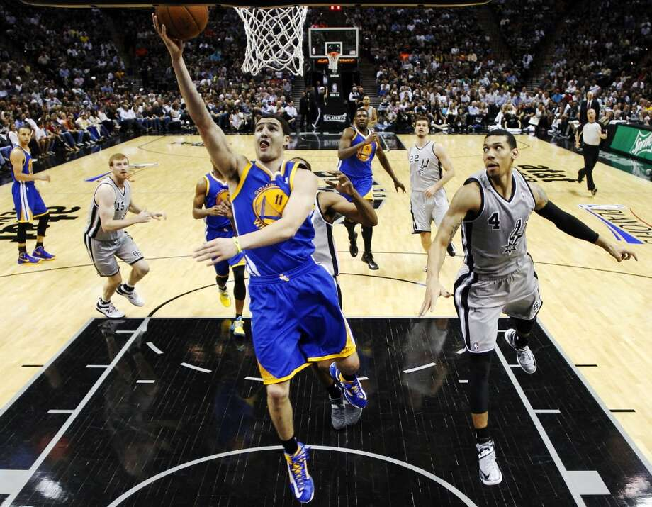 The Warriors' Klay Thompson (11) scores as the Spurs' Danny Green (4) defends during the first half of Game 2 in their Western Conference semifinal NBA basketball playoff series, Wednesday, May 8, 2013, in San Antonio.
