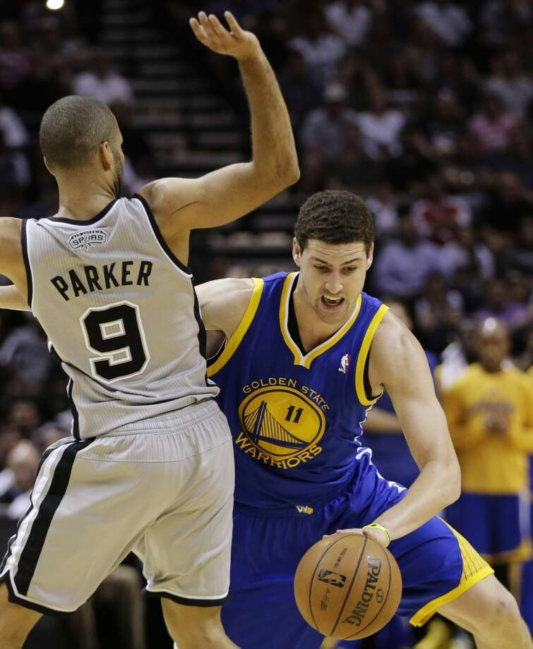 The Warriors' Klay Thompson (11) drives around the Spurs' Tony Parker (9) during the second half in Game 2 of a Western Conference semifinal NBA basketball playoff series, Wednesday, May 8, 2013, in San Antonio.