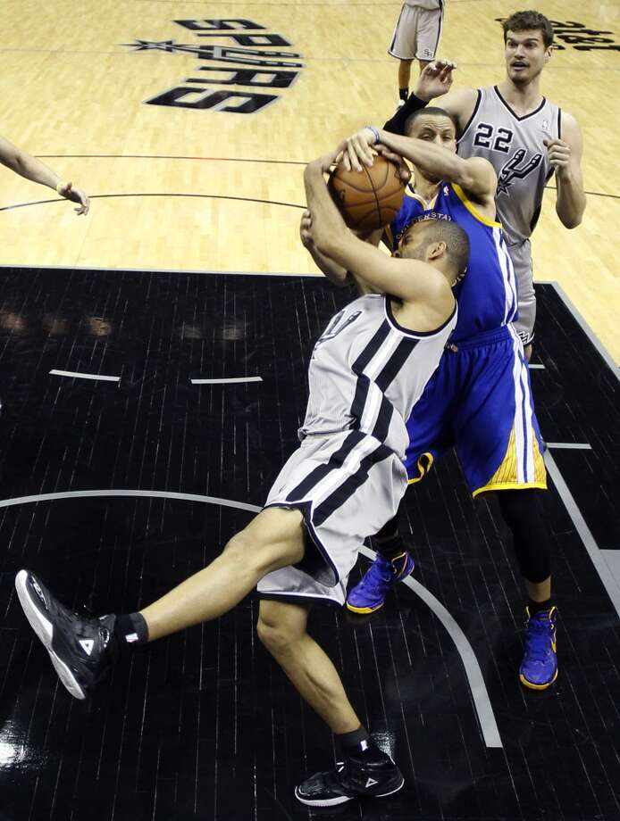 The Spurs' Tony Parker (9) is defended by the Warriors' Stephen Curry during the second half as Tiago Splitter (22) looks on in Game 2 of a Western Conference semifinal NBA basketball playoff series, Wednesday, May 8, 2013, in San Antonio.