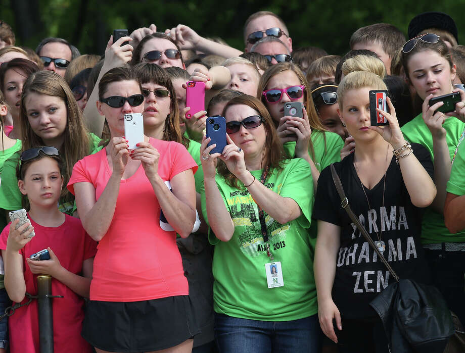 Women take pictures with their smartphones as they wait for HRH Prince Harry to arrive during the second day of his visit to the United States at Arlington National Cemetery on May 10, 2013 in Arlington, Virginia. HRH will be undertaking engagements on behalf of charities with which the Prince is closely associated on behalf also of HM Government, with a central theme of supporting injured service personnel from the UK and US forces. Photo: Chris Jackson, Getty Images / 2013 Getty Images