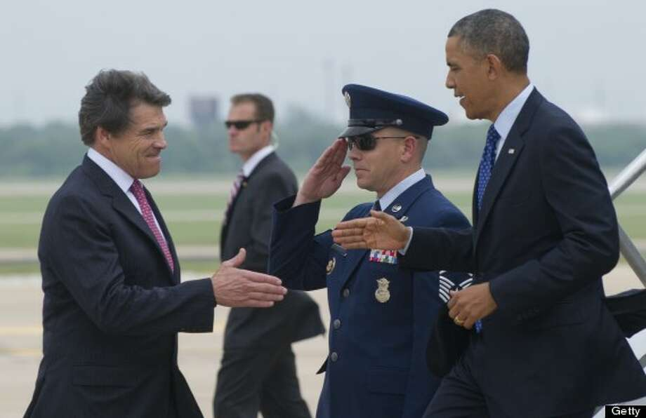 US President Barack Obama reaches out to shake hands with Texas Governor Rick Perry (L) after arriving on Air Force One at Austin-Bergstrom International Airport in Austin, Texas, May 9, 2013. Obama will speak on the economy and job creation. AFP PHOTO / Saul LOEB Photo: SAUL LOEB, AFP/Getty Images / 2013 AFP