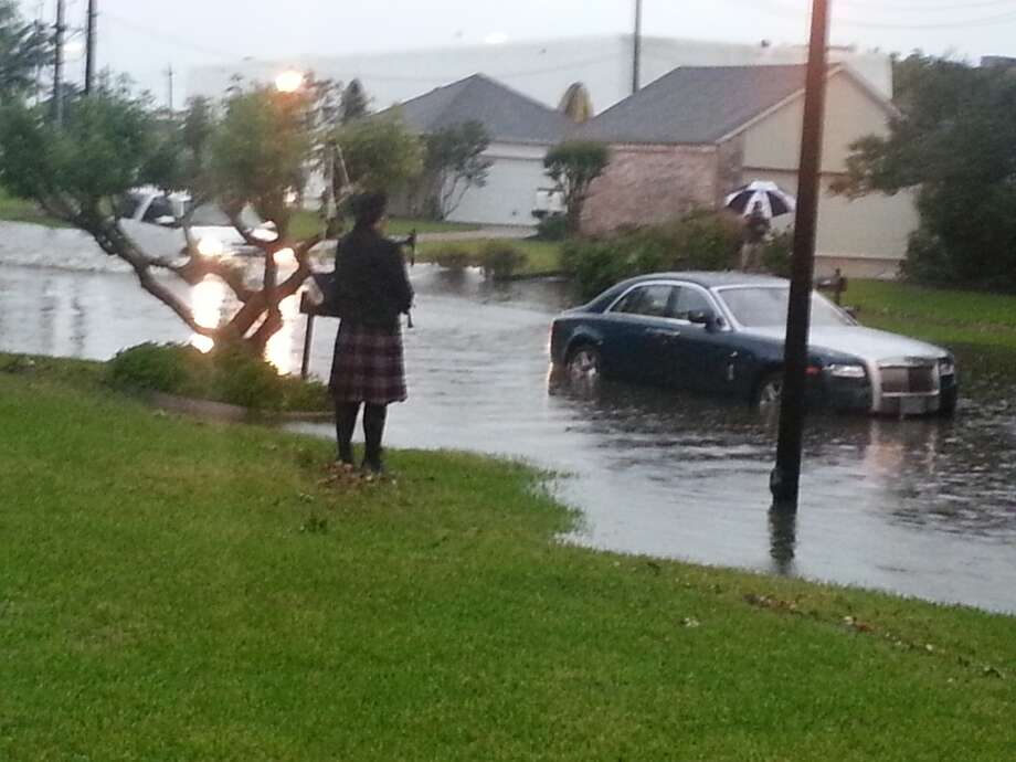 Sugar Creek on Country Club Boulevard in Sugar Land. Flooded Rolls and bag pipes.