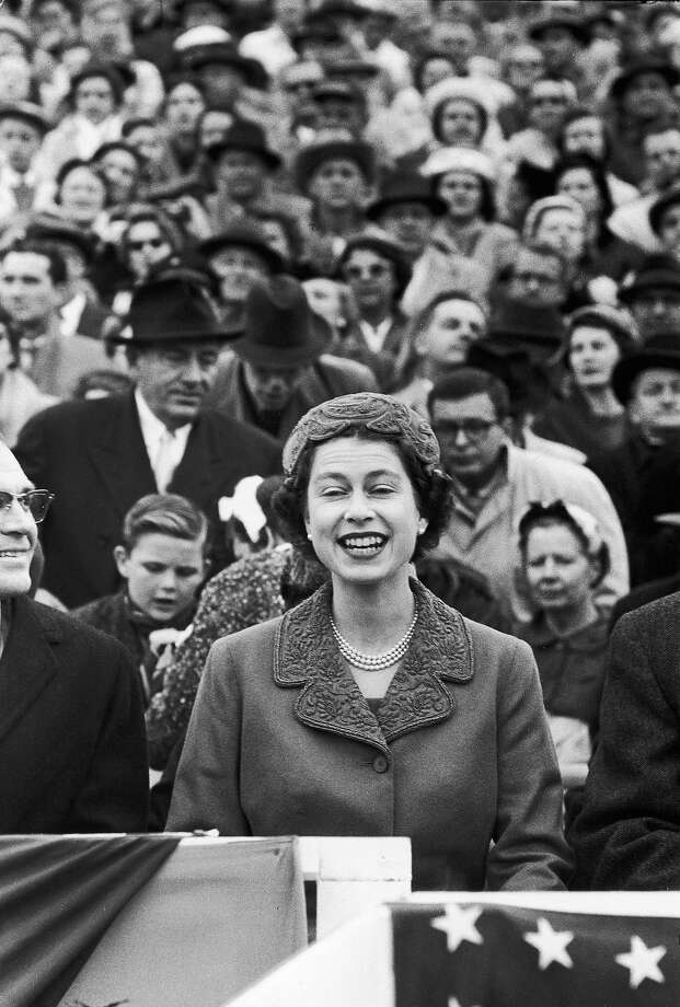 1957: Queen Elizabeth, a first-time spectator of Amer. football, sitting gleefully in the stands w. others while watching Univ. of Maryland vs. Univ. of North Carolina football game at College Park's Byrd Stadium during her official visit to the US. Photo: Alfred Eisenstaedt, Time & Life Pictures/Getty Image / Time Life Pictures