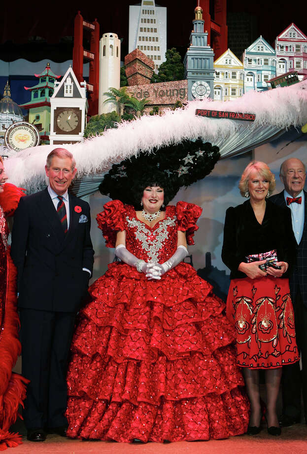 "2005: Prince Charles, Prince of Wales (L) and Camilla, Duchess of Cornwall (R) pose with Val Diamond, wearing a San Francisco skyline hat, after they watched the musical ""Beach Blanket Babylon"" in San Francisco. Photo: Pool, Getty Images / 2005 Getty Images"