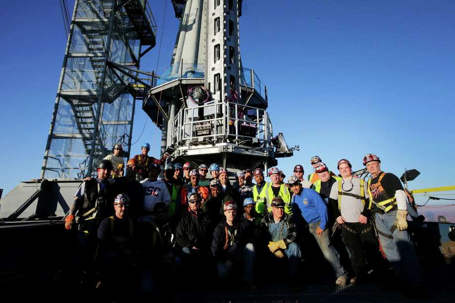 Iron workers pose for photos on the roof of One World Trade center before the final piece of spire is hoisted in place, Friday, May 10, 2013 in New York. The addition of the spire, and its raising of the building's height to 1,776 feet, would make One World Trade Center the tallest structure in the U.S. and third-tallest in the world. Photo: Mark Lennihan, AP / AP
