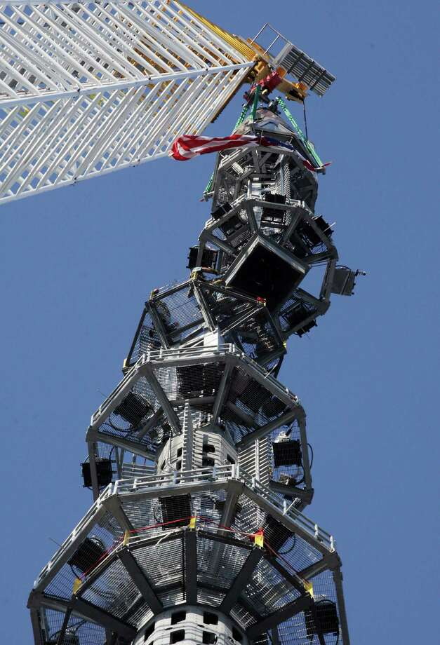 The final piece of spire is hoisted in place on top of One World Trade Center, Friday, May 10, 2013 in New York. The addition of the spire, and its raising of the building's height to 1,776 feet, would make One World Trade Center the tallest structure in the U.S. and third-tallest in the world. Photo: Mark Lennihan, AP / AP